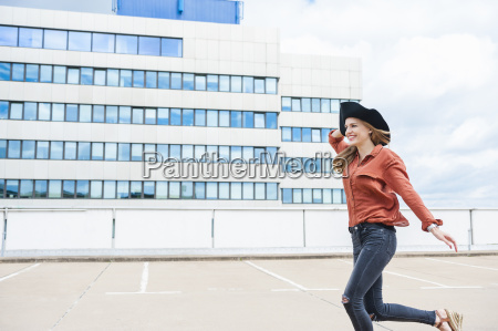 woman with hat running on roof