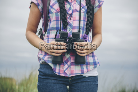woman holding binocular partial view