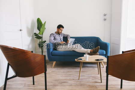 businessman sitting on couch in office
