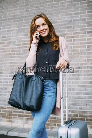 smiling young woman with wheeled luggage