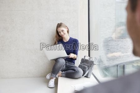 smiling young woman sitting at concrete
