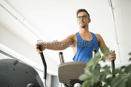 man exercising on elliptical bike in