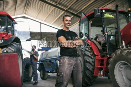 portrait of confident mechanic at tractor