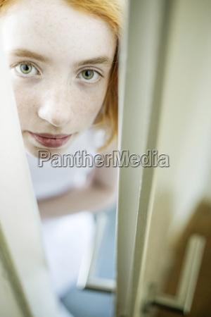 girl peeking through ajar door