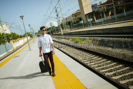 young man with suitcase walking at