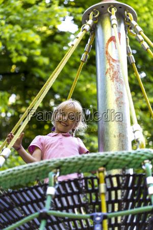 little girl in a nest swing