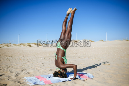 young woman doing a headstand on