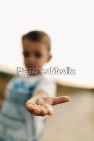snail on little boys palm