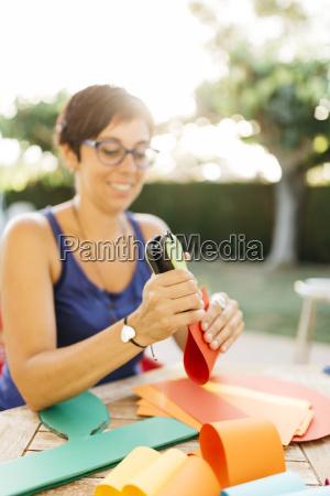 woman doing handicrafts at garden table