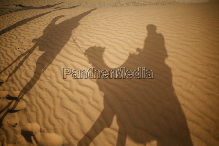shadows of people riding camels in