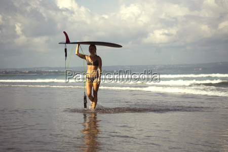 indonesia bali woman carrying her surfboard
