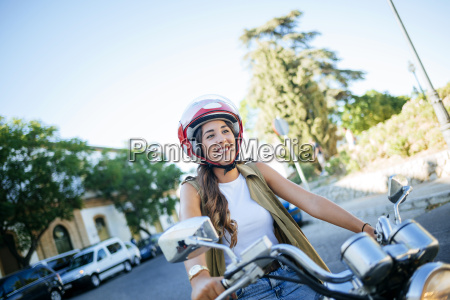 happy young woman riding motorcycle