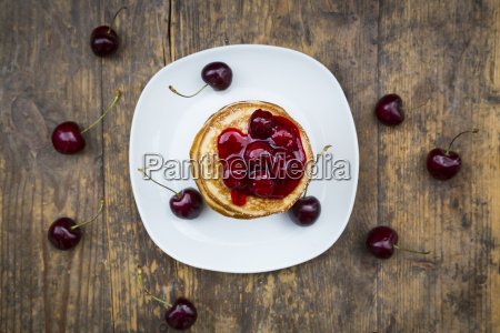 stack of american pancakes with cherries