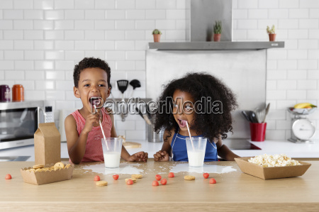 siblings drinking milk in the kitchen