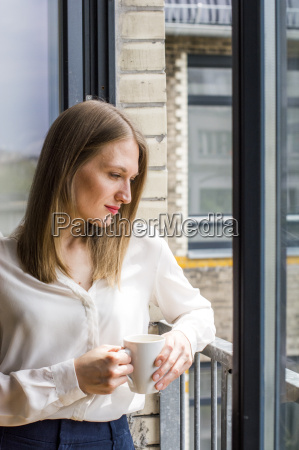 woman with coffee mug standing at