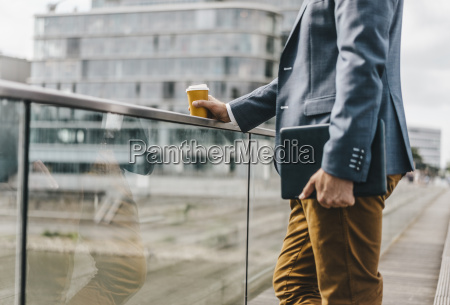 businessman standing on bridge with coffee
