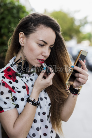 uk london young woman applying lipstick