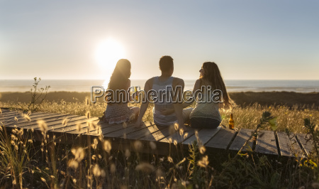 friends sitting on boardwalk at the