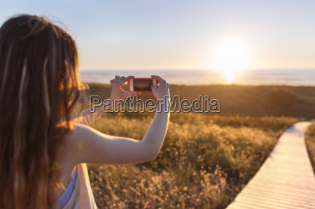 young woman photographing beach at sunset