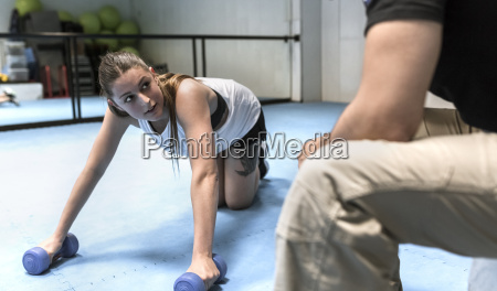 young woman in gym doing strength