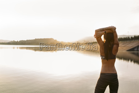 female athlete stretching at the sea