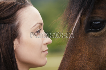 young woman and brown horse face