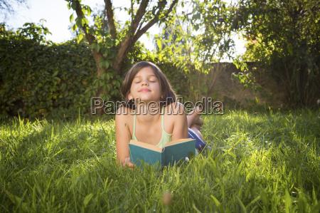 happy girl lying on meadow with