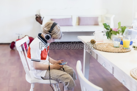 boy wearing headphones looking at cell