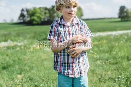 boy outdoors holding glass with jelly