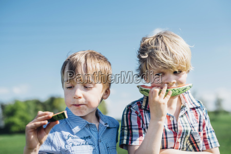 two boys outdoors eating watermelon