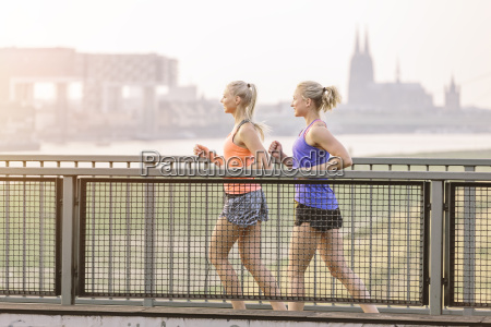 two young women running on bridge