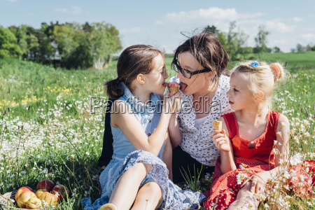 mother and two girls in meadow