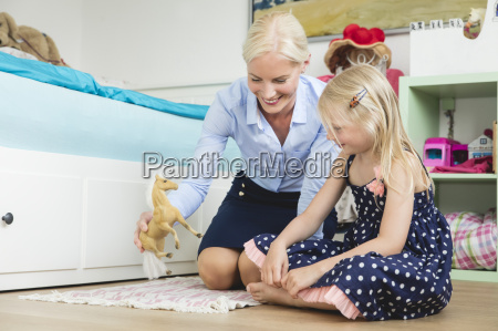businesswoman playing with her little daughter