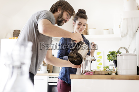 couple in kitchen preparing coffee