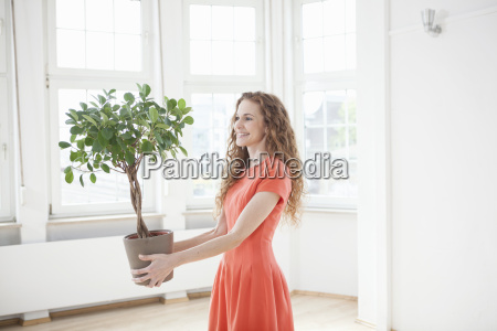 smiling woman holding plant in empty