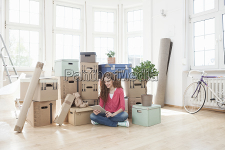 woman surrounded by cardboard boxes using