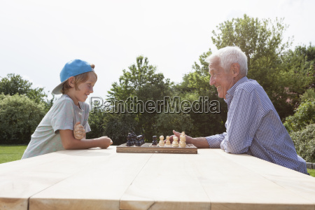 grandfather and grandson playing chess in