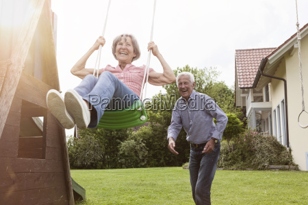 playful senior couple with swing in