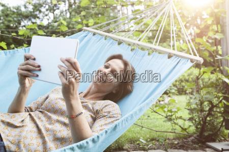 smiling woman using digital tablet in