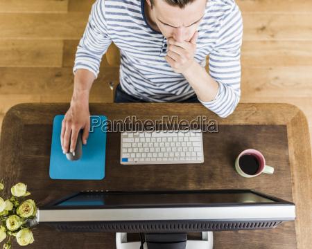 man at wooden desk thinking