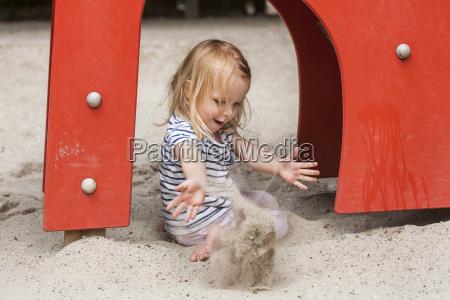 blond little girl in sandbox on