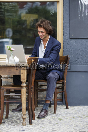 smiling young businessman working with laptop