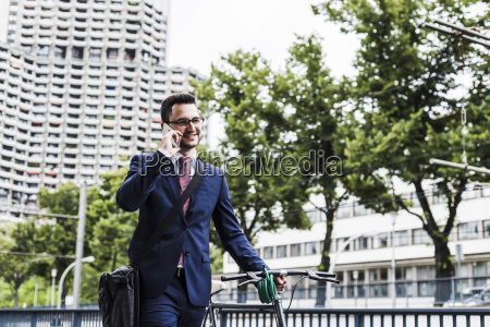 businessman with bicycle walking in the
