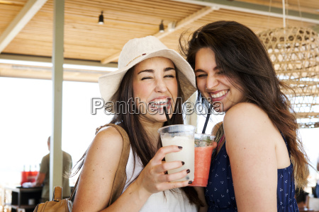 two young woman drinking cocktails in