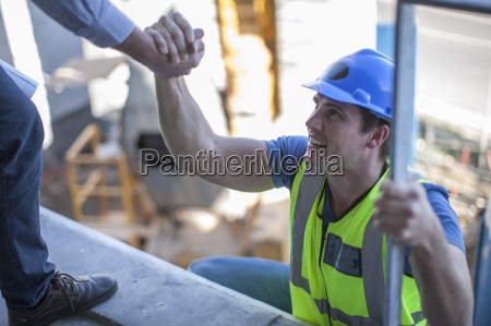 construction worker shaking hands on construction