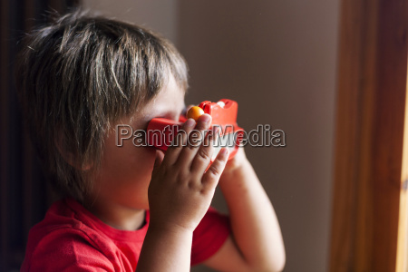 little boy playing with view master