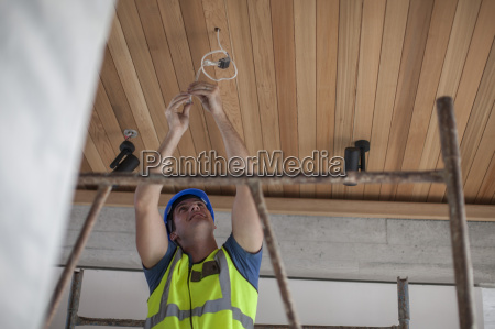 electrician fixing cable at ceiling