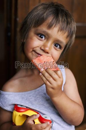 portrait of funny little boy eating