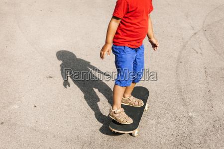 little boy standing on skateboard partial