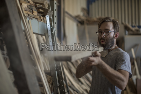 carpenter blowing dust from a piece